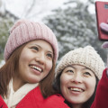 Two women taking picture with cell phone
