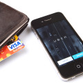 Cell phone with Uber logo on screen and wallet with Visa sticking out