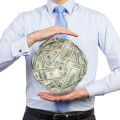 Businessman holding ball of money