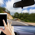Hands holding phone in driver's seat of car with background in motion